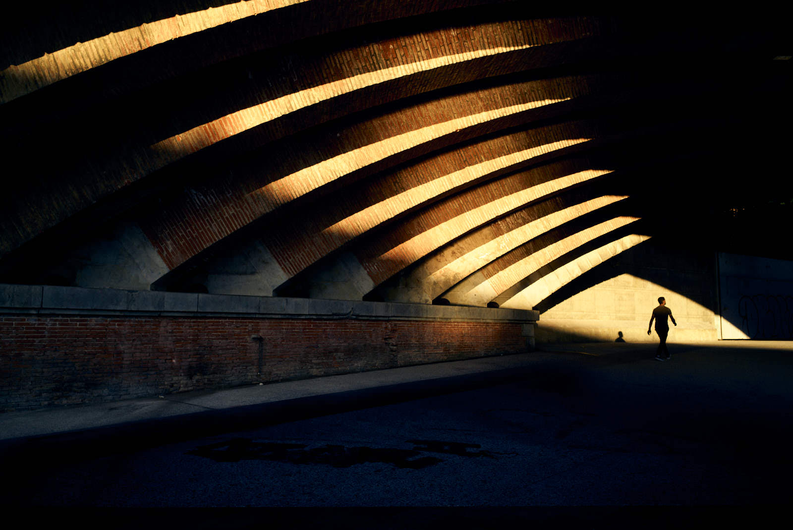 man passing under a bridge with light from sunset in toulouse